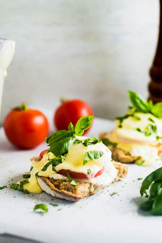 eggs benedict topped with fresh basil on a white surface with whole tomatoes in the background