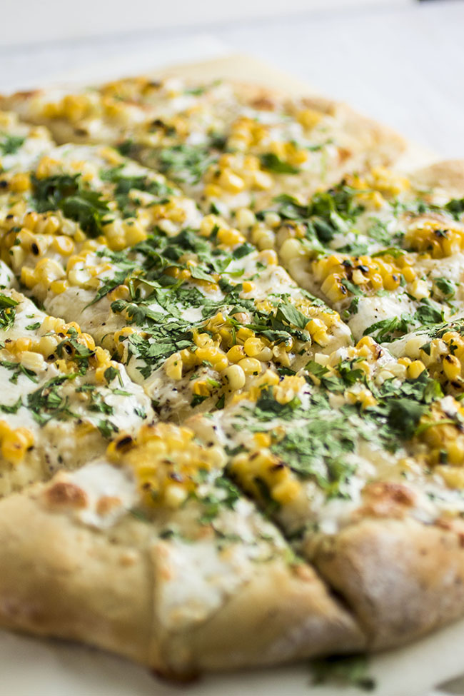 Square cut pizza topped with grilled corn and chopped cilantro on a white background