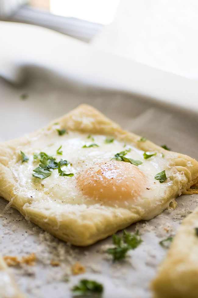 sunny side up egg on puff pastry with chopped parsley in front of window