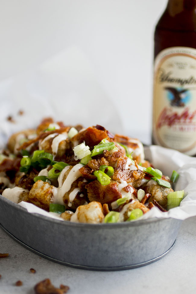 Tater tots in a metal tin topped with cheese, bacon, and green onions on a white background