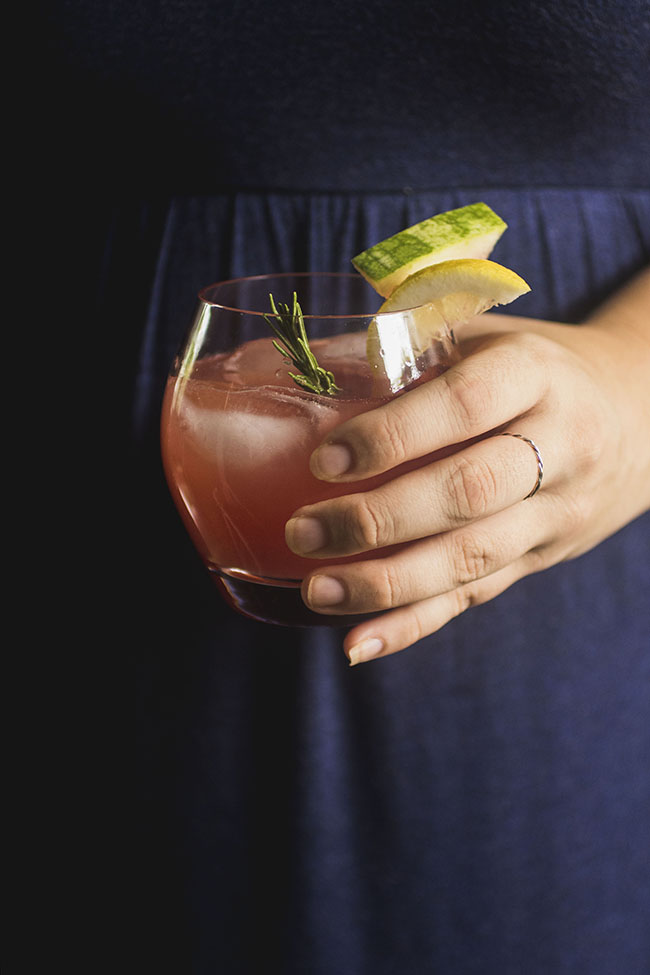 woman in blue dress hand holding rosemary and watermelon cocktail