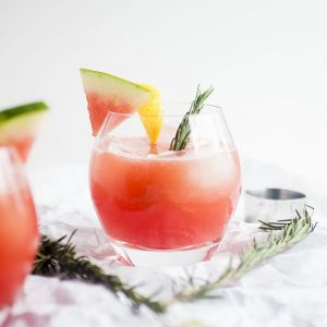glass with pink cocktail garnished with watermelon slice and fresh rosemary on a white background