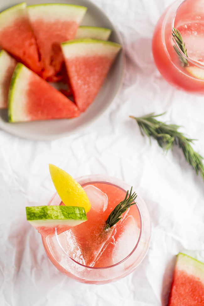 2 glasses filled with rosemary and watermelon cocktail and ice cubs surrounded by rosemary sprigs and plate of fresh watermelon slices