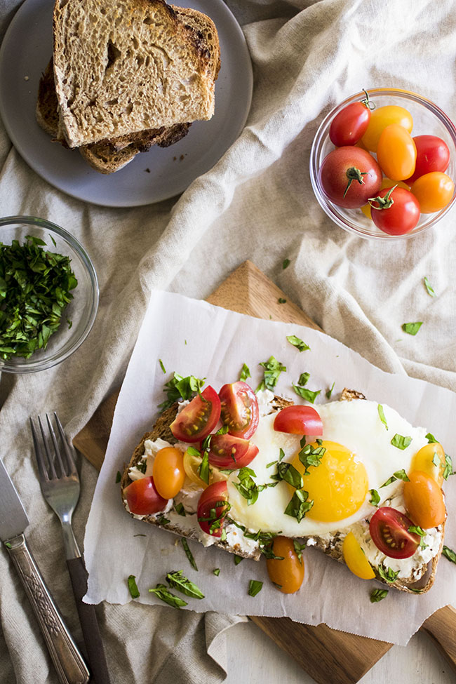 Overhead photo of fried egg topped with cherry tomatoes and fresh basil, surrounded by dishes of tomatoes, basil, and toast