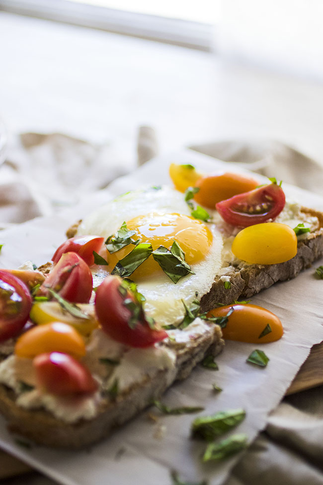 Sunny side up egg on top of sourdough toast topped with quartered cherry tomatoes and chopped basil in front of a kitchen window.