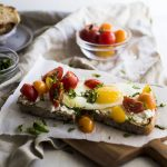 Sunny side up egg on toast with cherry tomatoes and chopped basil