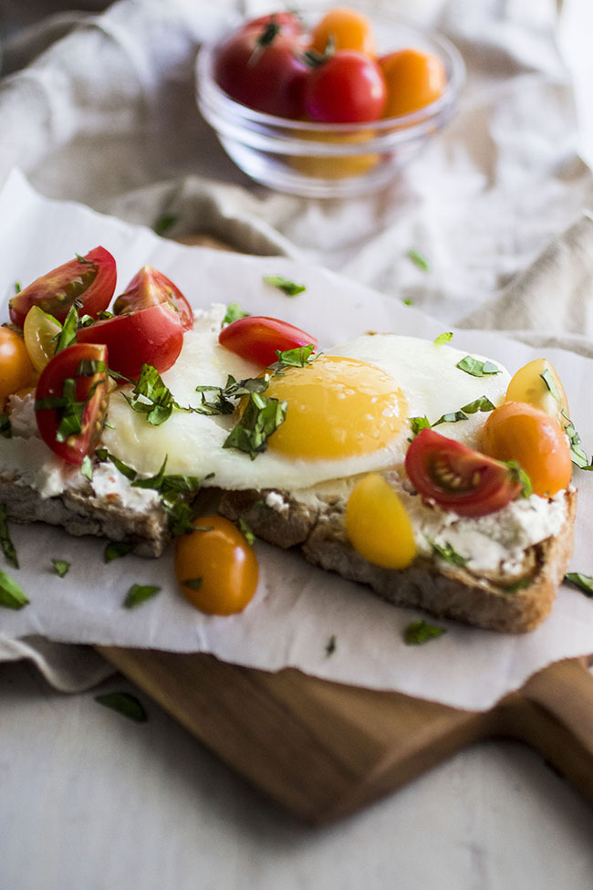 Sunny side up egg on top of toast with goat cheese, quartered cherry tomatoes, and chopped basil on a white linen napkin