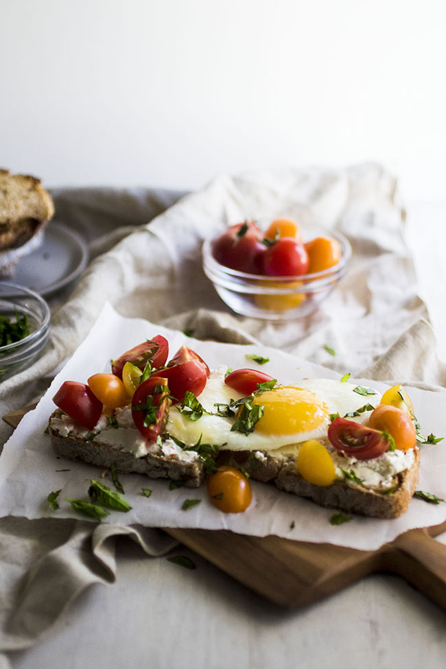 sunny side up egg on top of toast surrounded by cherry tomatoes and fresh basil in front of a white background