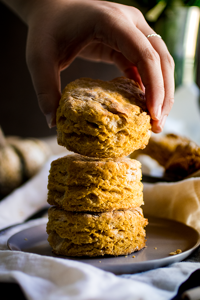 Woman's hand stacking a pumpkin biscuit on top of two other biscuits with a dark background