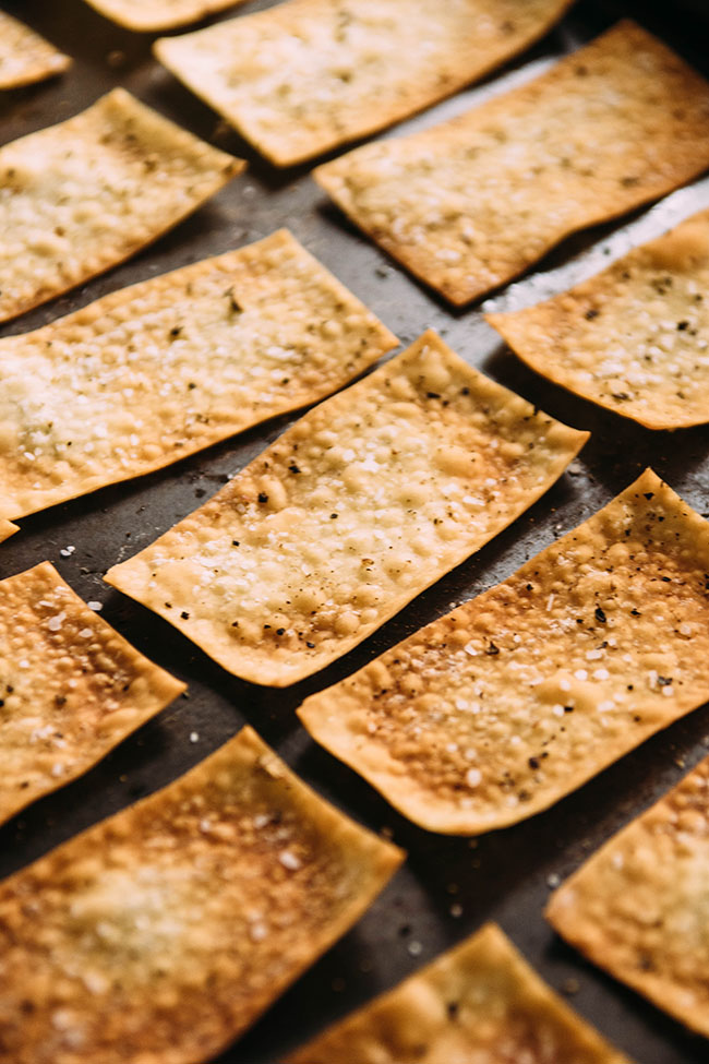 Side photograph of homemade crackers with salt and pepper in a single layer on a dark background