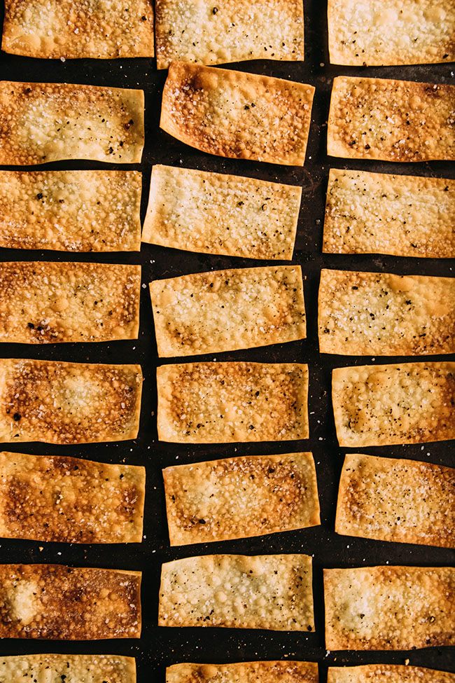 Overhead photo of homemade crackers in three straight lines on a dark background
