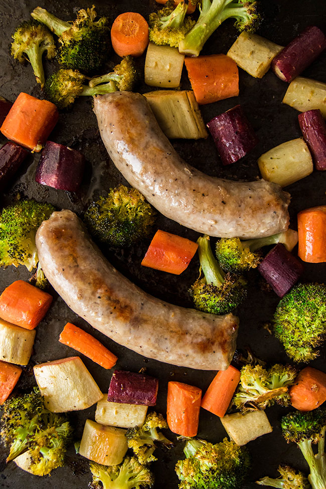 Close-up overhead photo of cooked sausage on a sheet pan surrounded by chopped carrots, parsnips, and broccoli.