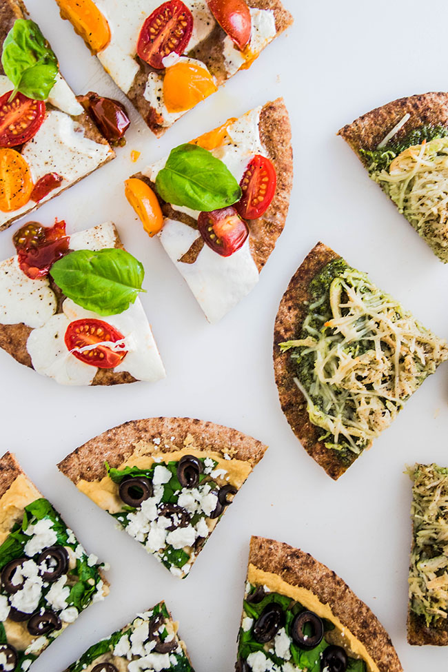 Overhead photo of three pita bread pizzas with various colorful toppings cut into slices on a white background