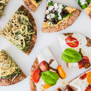 Overhead photo of three pita bread pizzas cut into slices on a white background