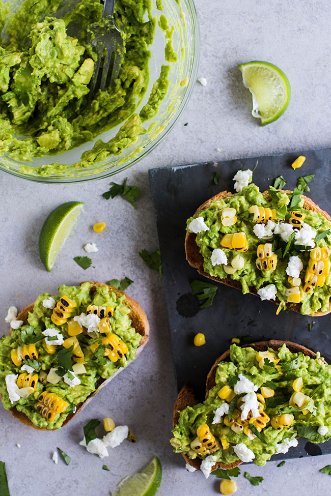 Overhead photo of three pieces of toast topped with mashed avocado, crumbled goat cheese, grilled corn kernels and chopped cilantro on a light grey background