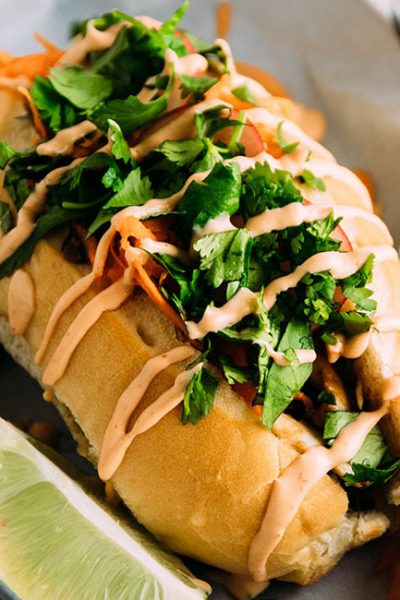 Side photo of a banh mi sandwich drizzled with spicy mayonnaise with a lime wedge on the side