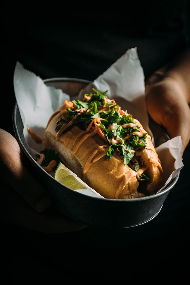 Side photo of hands holding a metal dish with a sandwich roll stuffed with fish and fresh vegetables with a dark background