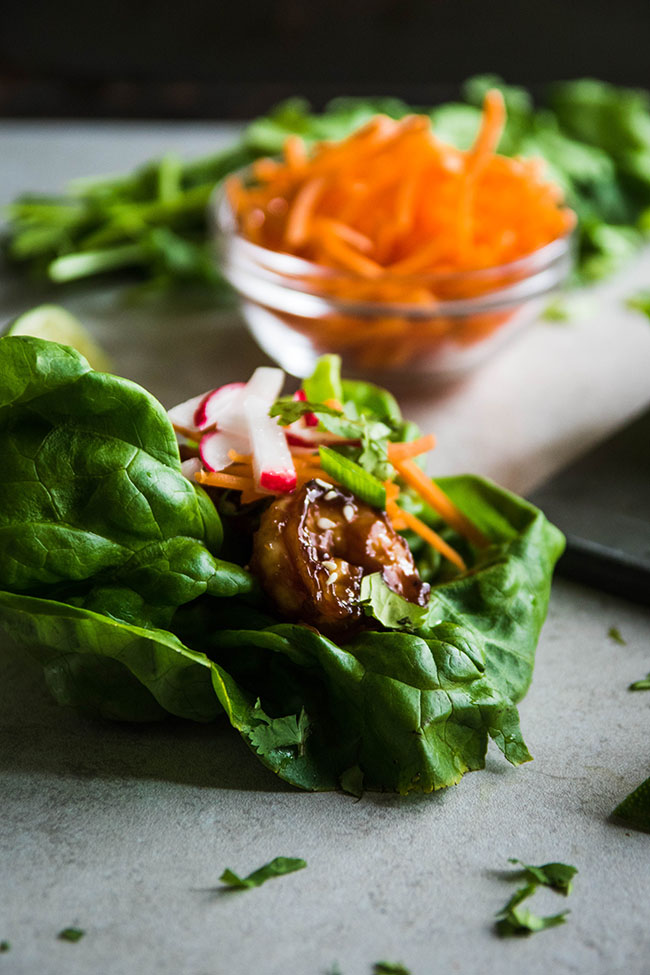 Side photograph of cooked shrimp with hoisin sauce atop a large butter lettuce leaf with shredded carrots in the background