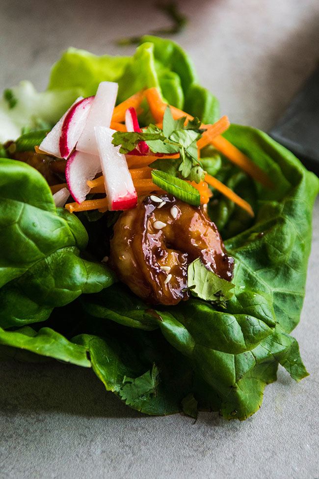 Closeup photo of cooked shrimp with hoisin sauce and sesame seeds topped with radish, cilantro and carrots inside a butter lettuce leaf