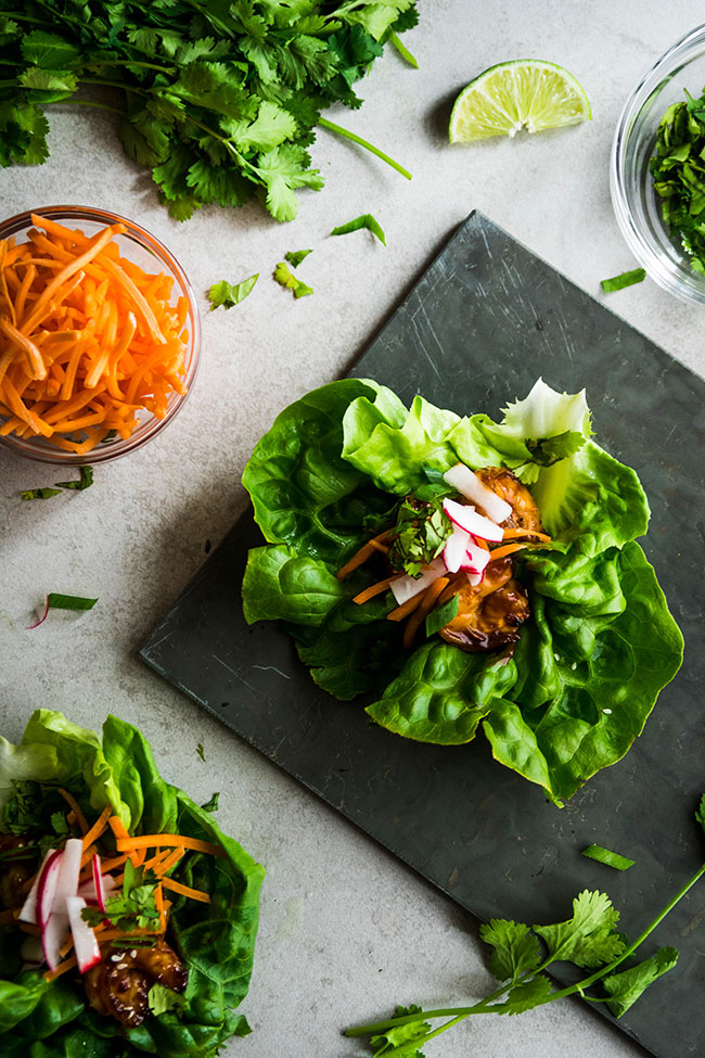 Overhead photo of butter lettuce wraps surrounded by cilantro, lime, and shredded carrots on a light grey background
