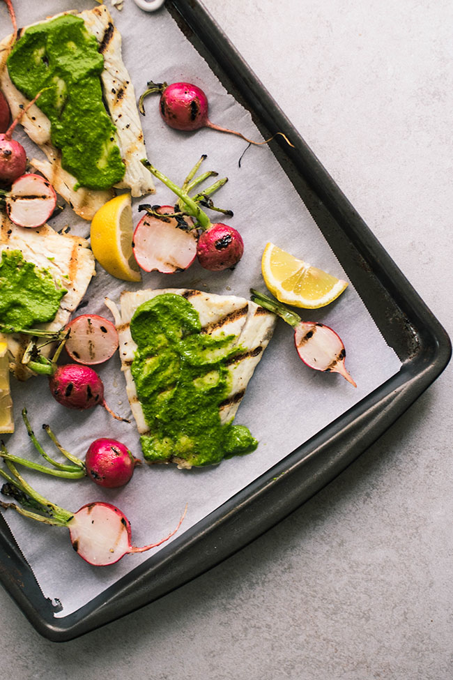 Overhead photo of grilled barramundi fillets on a sheet pan topped with green pesto and surrounded by grilled radishes.