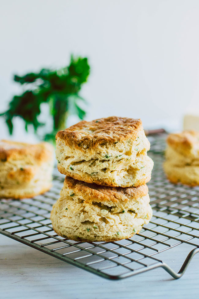 Side photo of two buttermilk biscuits on a wire cooling rack with a white background.