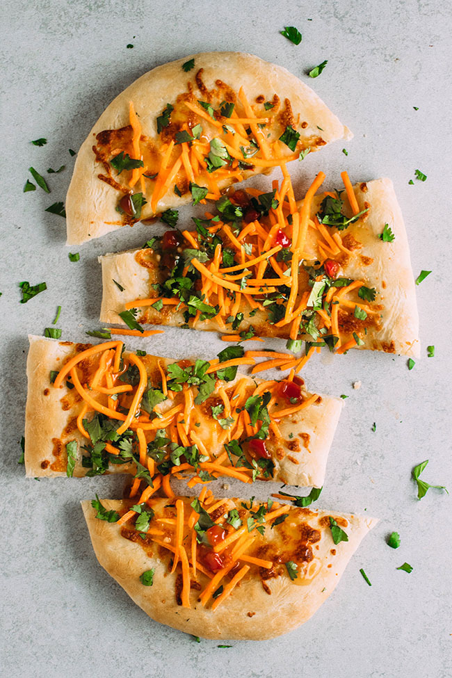 Overhead photo of oval shaped pizza topped with carrots and cilantro cut into four pieces and pulled apart on a light background