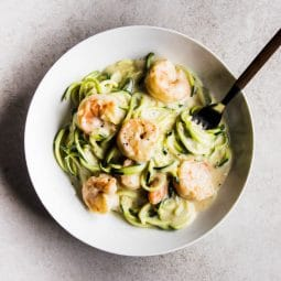 Overhead square photo of spiralized zucchini noodles and cooked shrimp in a white bowl