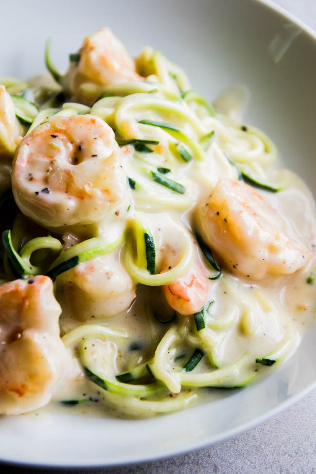 Side photograph of zucchini noodles and cooked shrimp with white cream sauce in a white bowl