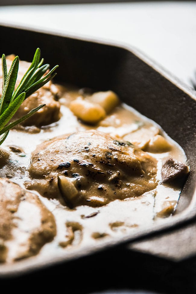 Creamy one pot chicken recipe in a cast iron skillet with mushrooms, potatoes, spinach, and parmesan garlic sauce.