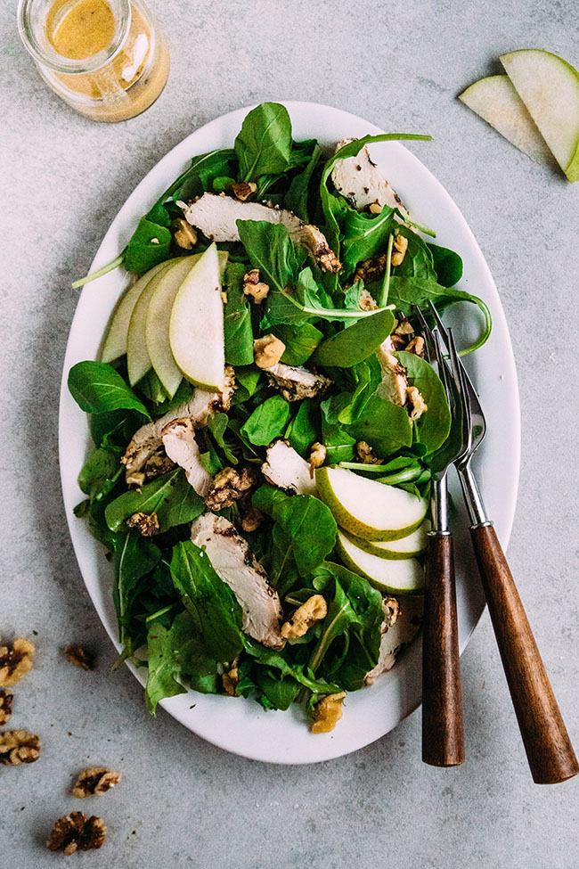 Overhead photo of a arugula salad on a white platter with grilled chicken, sliced pears, walnuts, and wooden serving utensils.