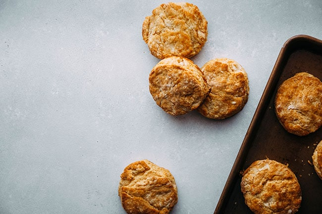 overhead photo of part of a baking sheet with some sweet potato biscuits on the baking sheet and some biscuits on the light grey table next to the pan.