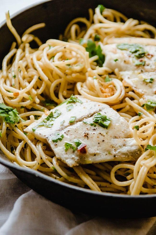 Seared white fish atop plain spaghetti in a cast iron skillet