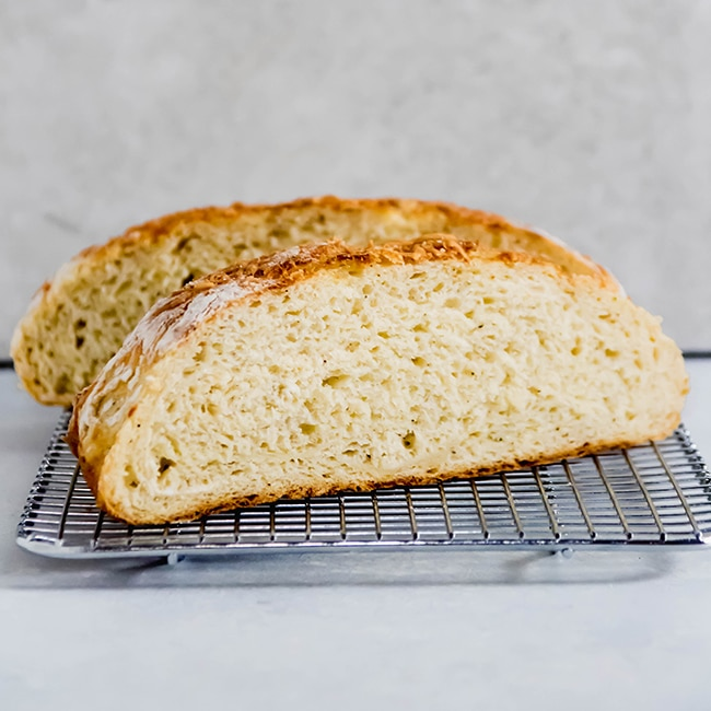 Asiago bread sliced in half and sitting on a wire cooling rack.