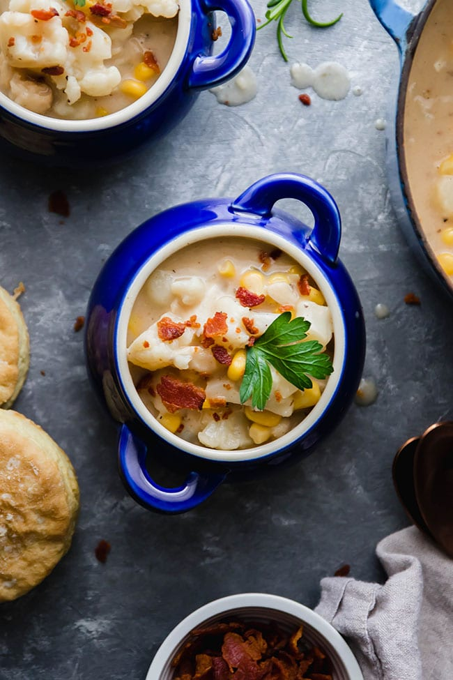 Overhead photo of two small blue bowls of fish chowder topped with bacon and parsley on a silver background, surrounded by chowder ingredients