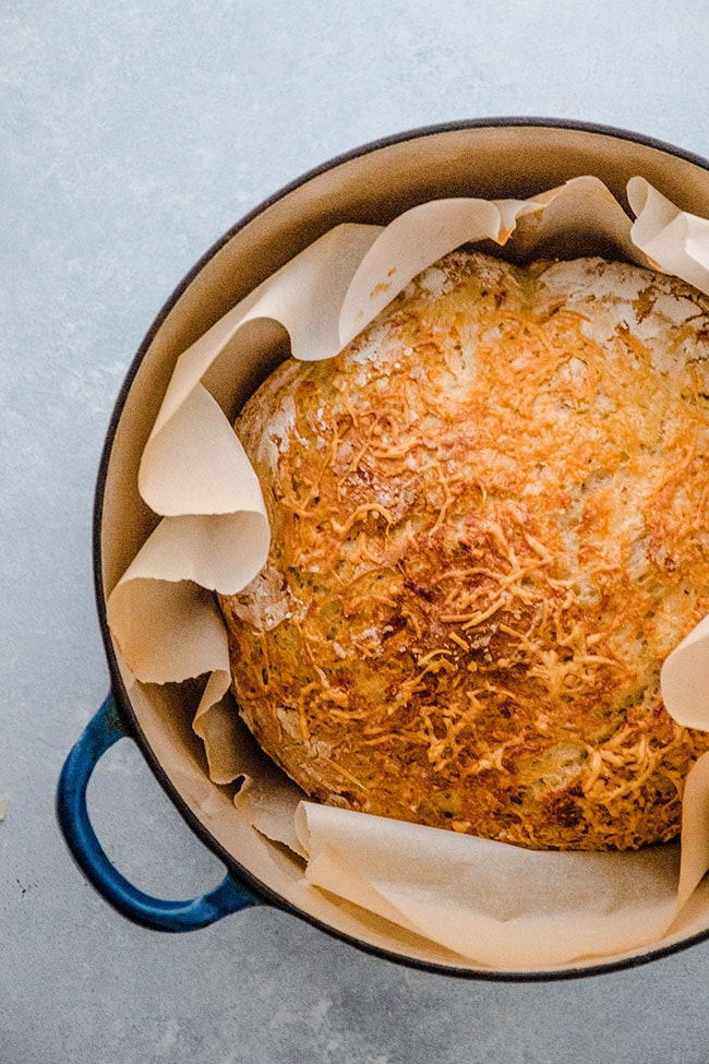 Overhead photo of asiago bread wrapped in parchment paper in a blue dutch oven on a white background