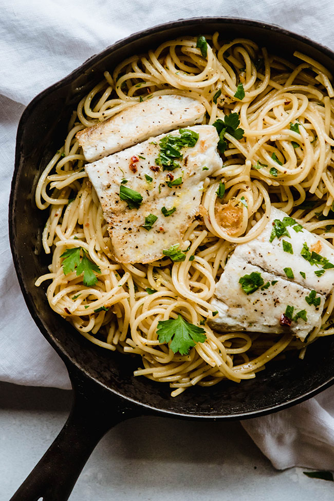 Overhead photo of a cast iron skillet filled with lemon garlic pasta and topped with seared white fish and fresh parsley
