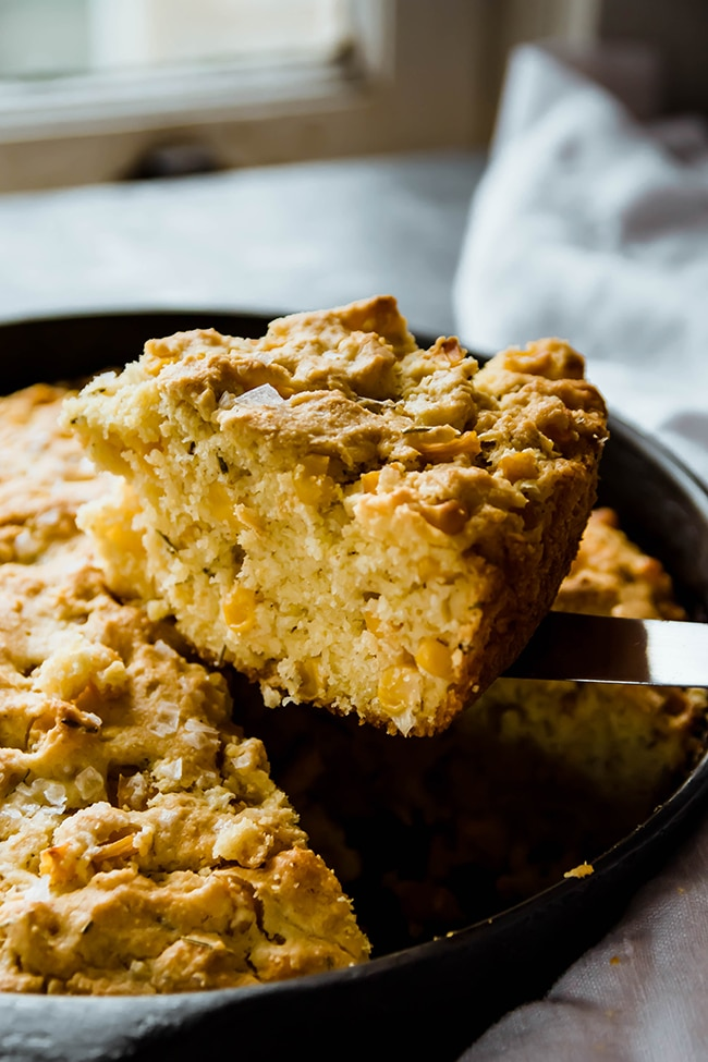 Knife lifting a piece of cornbread out of a cast iron skillet