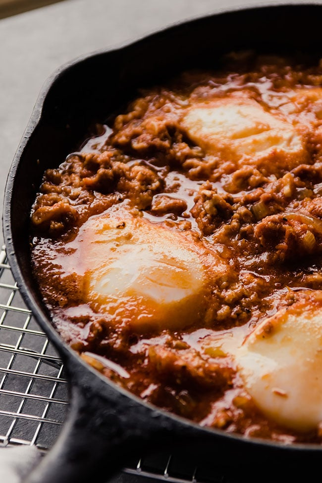 baked eggs in a cast iron skillet with chorizo and tomato sauce