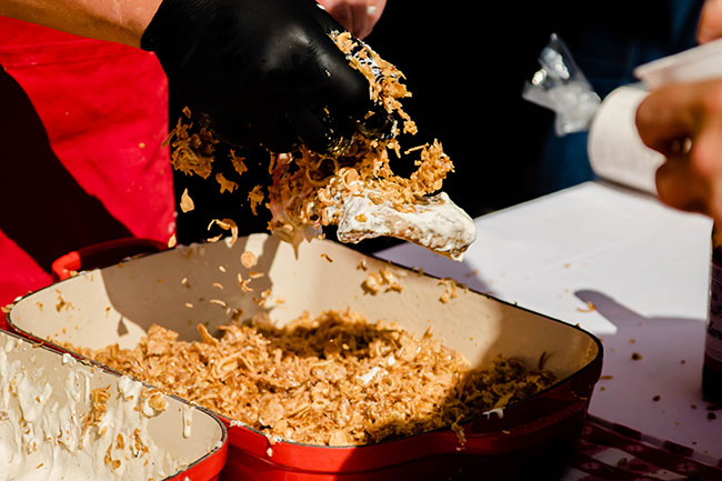 bacon being coated with crispy breadcrumbs over a red baking dish