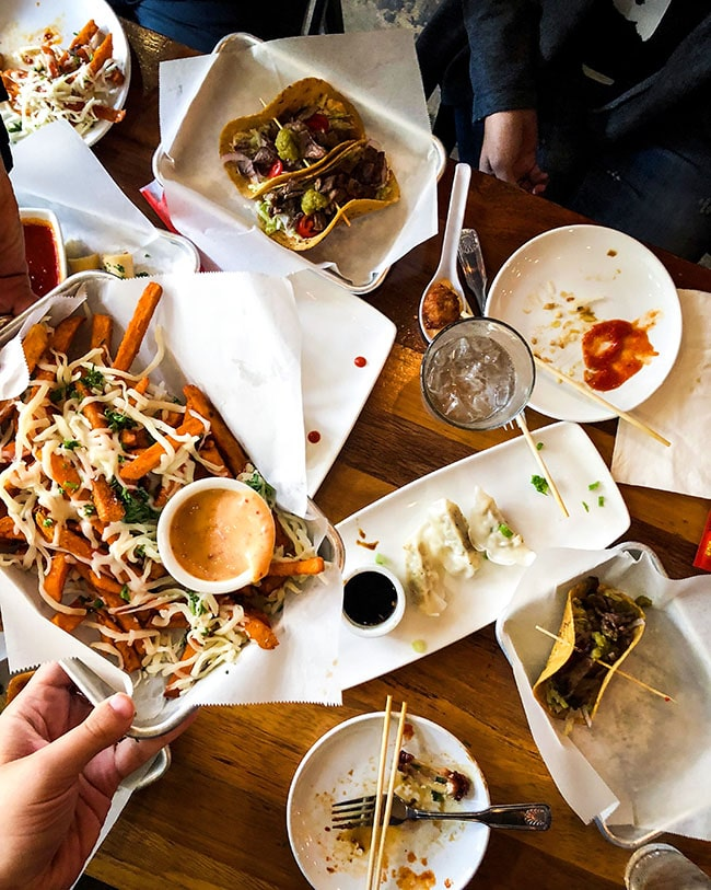 overhead photo of hands passing a plate of sweet potato fries over a table of food