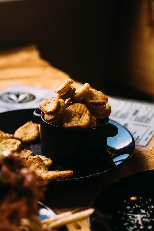 black dish filled with fried pickles on a wood table