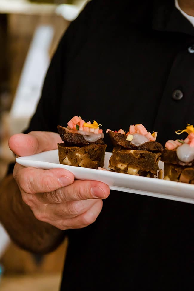 Man's hand holding a white plate with appetizers