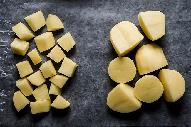 overhead photo of a pile of diced potatoes next to a pile of halved peeled potatoes for a size comparison