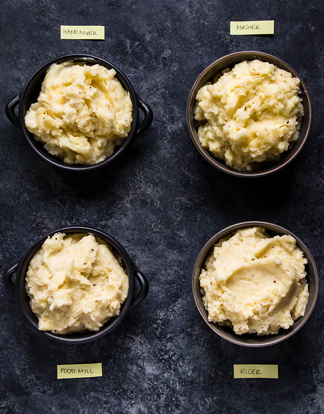 overhead photo of four bowls of mashed potatoes, each labeled with a different mashing method