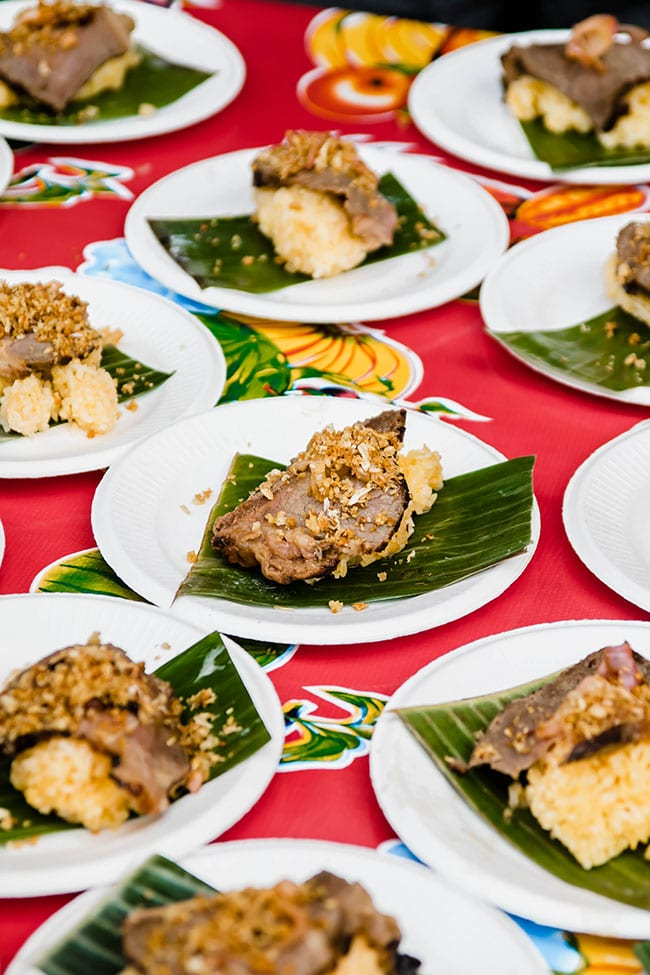 Appetizer bites of meat and rice on small white plates on a red floral tablecloth
