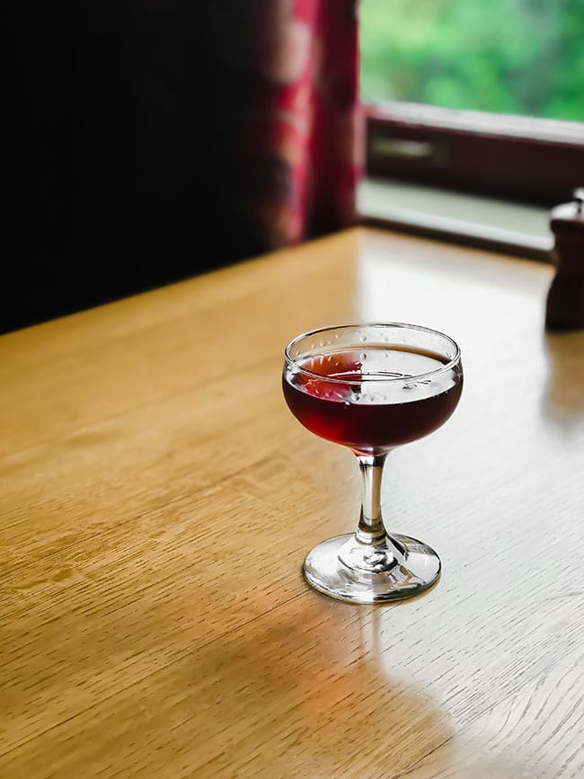manhattan cocktail on a wood table next to a window