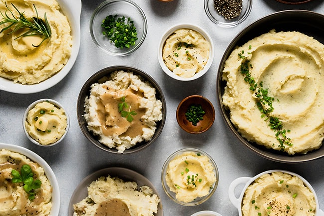 Overhead photo of multi-colored bowls, all full of mashed potatoes with various toppings