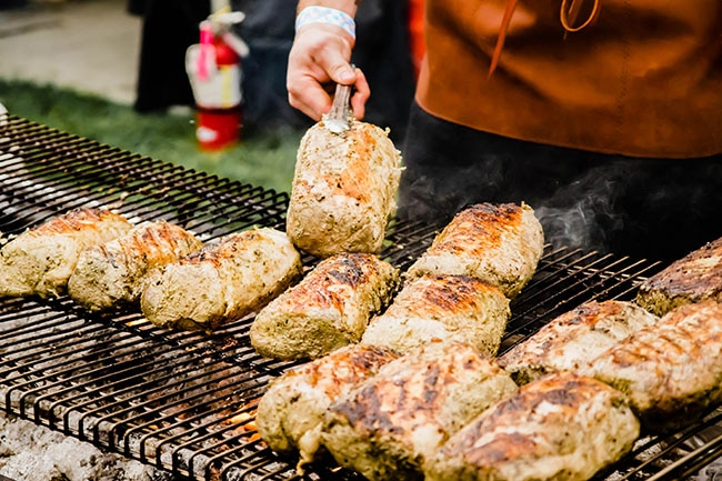man's hands using tongs to flip pork rounds over on a large grill