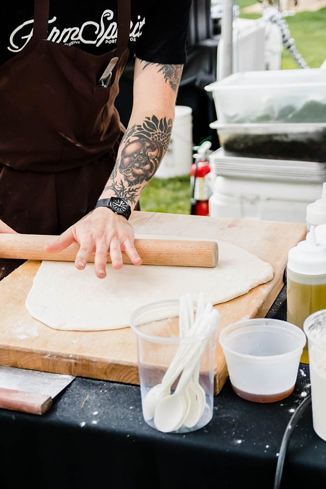 man's hands rolling pizza dough into a circle with a wood rolling pin